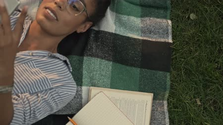 campus universitario : Top view of Happy pretty african woman in eyeglasses using smartphone while lying on plaid in the park Archivo de Video