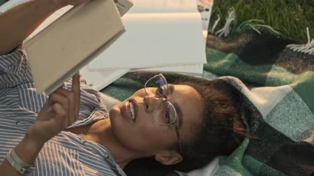 czytanie : Top view of Happy pretty african woman in eyeglasses reading book while lying on plaid in the park