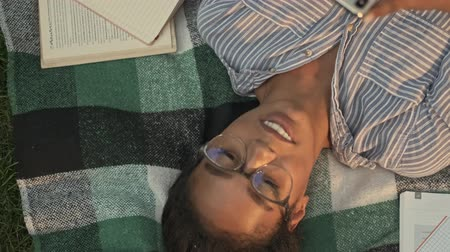 campus universitario : Top view of Cheerful pretty african woman in eyeglasses using smartphone while lying on plaid in the park