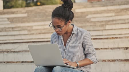 campus universitario : Serious pretty african woman in eyeglasses using laptop computer while sitting on stairs outdoors