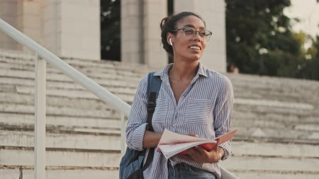 campus universitario : Calm pretty african woman in eyeglasses and earphones studying with notebook and writing something while sitting on stairs outdoors