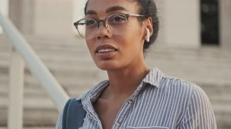 tajemnica : Calm pretty african woman in eyeglasses and earphones touching her hair and looking around while standing on stairs outdoors