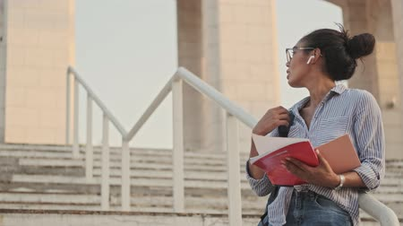 magasine : Concentrated pretty african woman in eyeglasses and earphones holding magazine and looking away while standing on stairs outdoors
