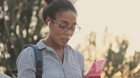časopis : Smiling pretty african woman in eyeglasses and earphones holding magazine and using smartphone while standing on stairs outdoors