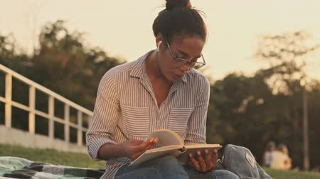 campus universitario : Calm pretty african woman in eyeglasses and earphones reading book while sitting on plaid in the park