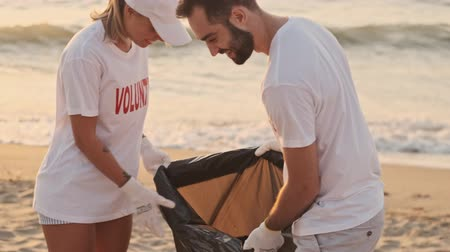 voluntary : An enthusiastic eco volunteers people are cleaning beach from plastic with trash bags at seaside Stock Footage