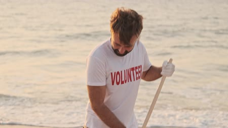 reciclagem : Young man volunteer is cleaning beach from rubbish