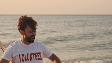 hevesli : An attractive young man volunteer is having fun while cleaning beach from rubbish Stok Video