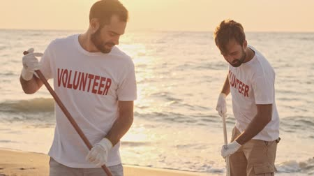 voluntary : Handsome young men volunteers are cleaning beach from rubbish using a rake