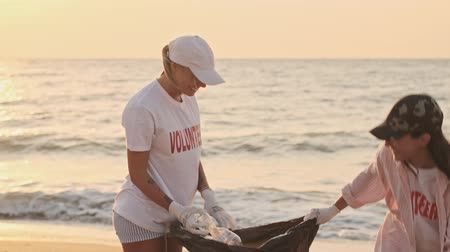 voluntary : Smiling enthusiastic eco volunteers girls are cleaning beach from plastic with trash bags at seaside