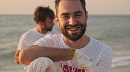 voluntary : A cheerful male volunteer is cleaning beach from plastic at seaside Stock Footage