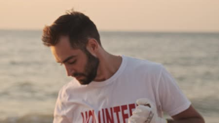waste water : Tired young man volunteer wipes sweat from his forehead while cleaning beach from rubbish at dawn