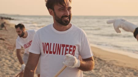 hevesli : Happy eco volunteers are cleaning beach from plastic with rakes at the seashore