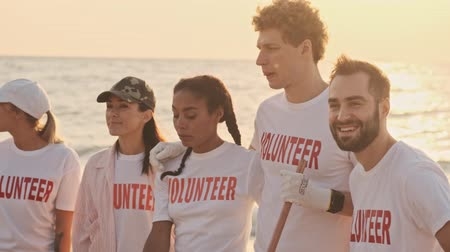 voluntary : Attractive young volunteers are getting ready to work with rakes and clean the beach from plastic at the seaside early in the morning Stock Footage