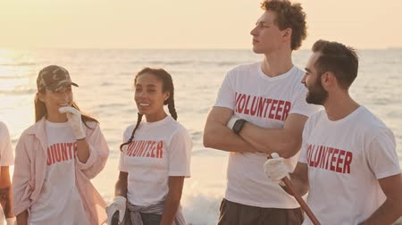 voluntary : Smiling young volunteers are getting ready to work with rakes and clean the beach from plastic at the seaside early in the morning