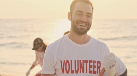 litière : A handsome smiling man volunteer is cleaning beach from plastic at seaside in the morning