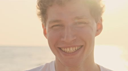 hevesli : Cropped view of young positive toothy man volunteer is laughing at the beach early in the morning Stok Video