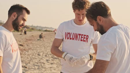hevesli : Handsome young male volunteers are cleaning beach from plastic with trash bags at seaside Stok Video