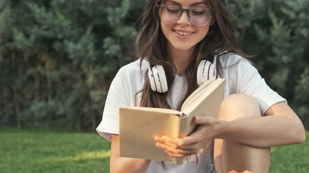 alluring : Happy positive young girl wearing glasses is smiling while reading a book outside in the city park