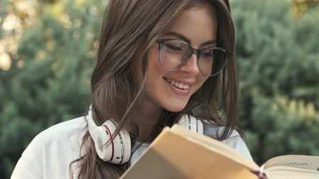 czytanie : Cropped view of an attractive happy young girl wearing glasses is smiling while reading a book outside in the city park Wideo