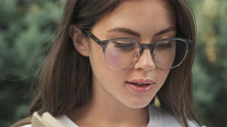 stroll : Calm beautiful young girl wearing glasses is reading a book while sitting outside in the city park Stock Footage