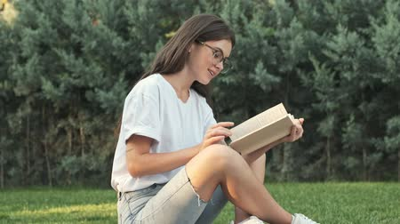 stroll : Beautiful young girl wearing glasses is reading a book while sitting outside in the city park in the summer