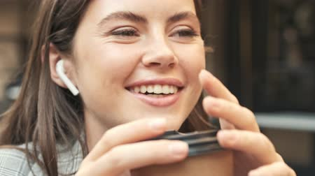 employed : A pretty smiling young woman is talking with someone using wireless headphones while sitting at the café outdoors