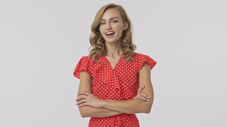 armen over elkaar : Happy pretty blonde woman in dress standing with crossed arms and wink with eye over grey background