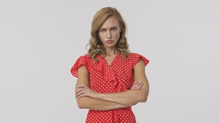 crossed : Displeased pretty blonde woman in dress standing with crossed arms and looking around over grey background