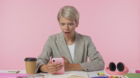 fotky : A stylish woman is watching something on her smartphone then finds out good news that makes her happy while sitting by the table over pink background