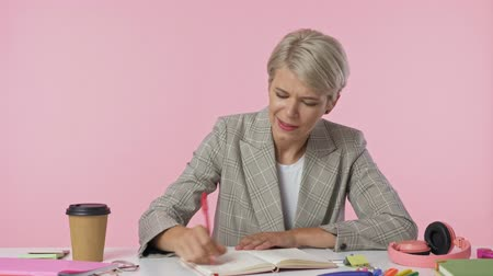 erros : A focused woman writes something on her notebook then crosses out, tears out the page and throws it isolated over pink background Vídeos