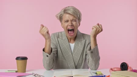 head over : A tired nervous young woman is screaming while touching her head isolated over pink background