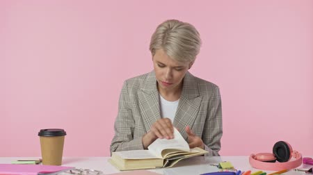 kopje thee : A beautiful young woman takes a book then puts on her glasses and starts to read isolated over pink background