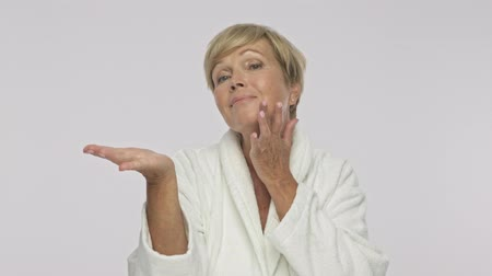 housecoat : A pleased adult woman with short blond hair wearing white housecoat holding copyspace on her palm isolated over white background