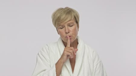 housecoat : A good-looking adult woman with short blond hair wearing white housecoat is showing a silence gesture isolated over white background