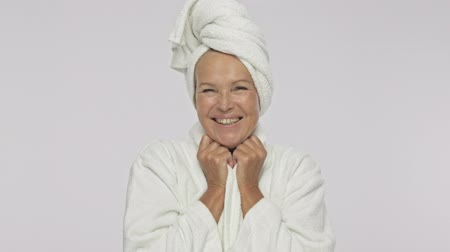 facecare : A beautiful adult woman wearing bathrobe and towel over her head is smiling isolated over white background