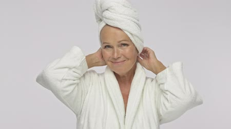 facecare : A beautiful adult woman wearing a bathrobe and is touching and correcting a towel over her head isolated over white background