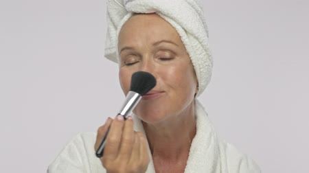 head over : A positive adult woman wearing bathrobe and towel over her head is applying cosmetics with makeup brush isolated over white background