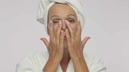 facecare : A nice adult woman wearing bathrobe and towel over her head is touching her face on massage lines isolated over white background Stock Footage