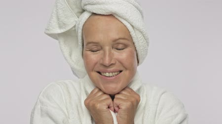 tur : An attractive adult woman wearing bathrobe and towel over her head is smiling isolated over white background