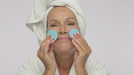 bölcs : An attractive adult woman wearing bathrobe and towel over her head is applying cosmetics with powder sponges isolated over white background