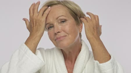 housecoat : A pretty adult woman with short blond hair wearing white housecoat is touching her hair while making natural hair style isolated over white background Stock Footage