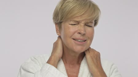 moudrý : An adult woman with short blond hair wearing white housecoat is showing her neck pain isolated over white background