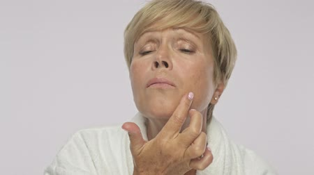 moudrý : A beautiful adult woman with short blond hair wearing white housecoat is touching her face like doing a face building procedure isolated over white background Dostupné videozáznamy