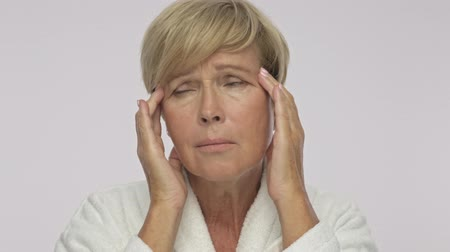housecoat : A sad upset adult woman with short blond hair wearing white housecoat is massaging her temples isolated over white background Stock Footage