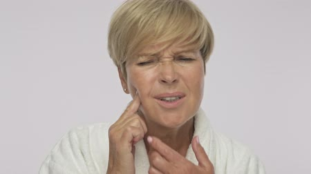 moudrý : A sad upset adult woman with short blond hair wearing white housecoat is showing her tooth pain isolated over white background