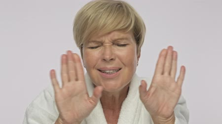 facecare : An adult woman with short blond hair wearing white housecoat is covering her ears isolated over white background