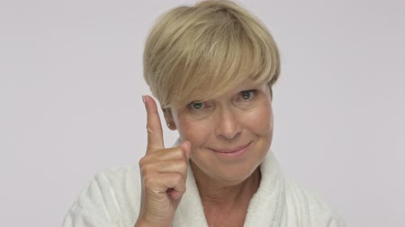 moudrý : An attractive adult woman with short blond hair wearing white housecoat is pointing her finger up like showing a good idea isolated over white background