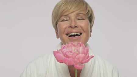 housecoat : A cute positive adult woman with short blond hair wearing white housecoat smells the aroma of a beautiful pink flower isolated over white background Stock Footage