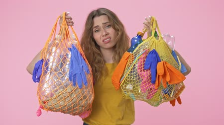 ninhada : A young sad woman is holding string bags with plastic waste and looking at the camera isolated over pink background